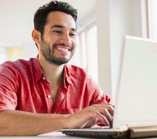 A man in a red shirt smiling at a laptop screen